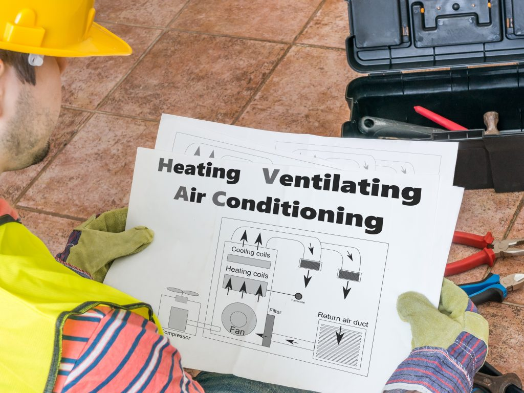 Repairman is looking at documentation of HVAC (Heating, Ventilating, Air Conditioning)