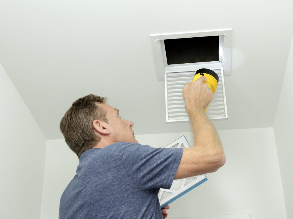 Checking Air Ducts in Home HVAC System. Man inspecting air ducts shining a flashlight through a small square ceiling vent into ducting pipes. Mature male examining the condition of air ducts at home.