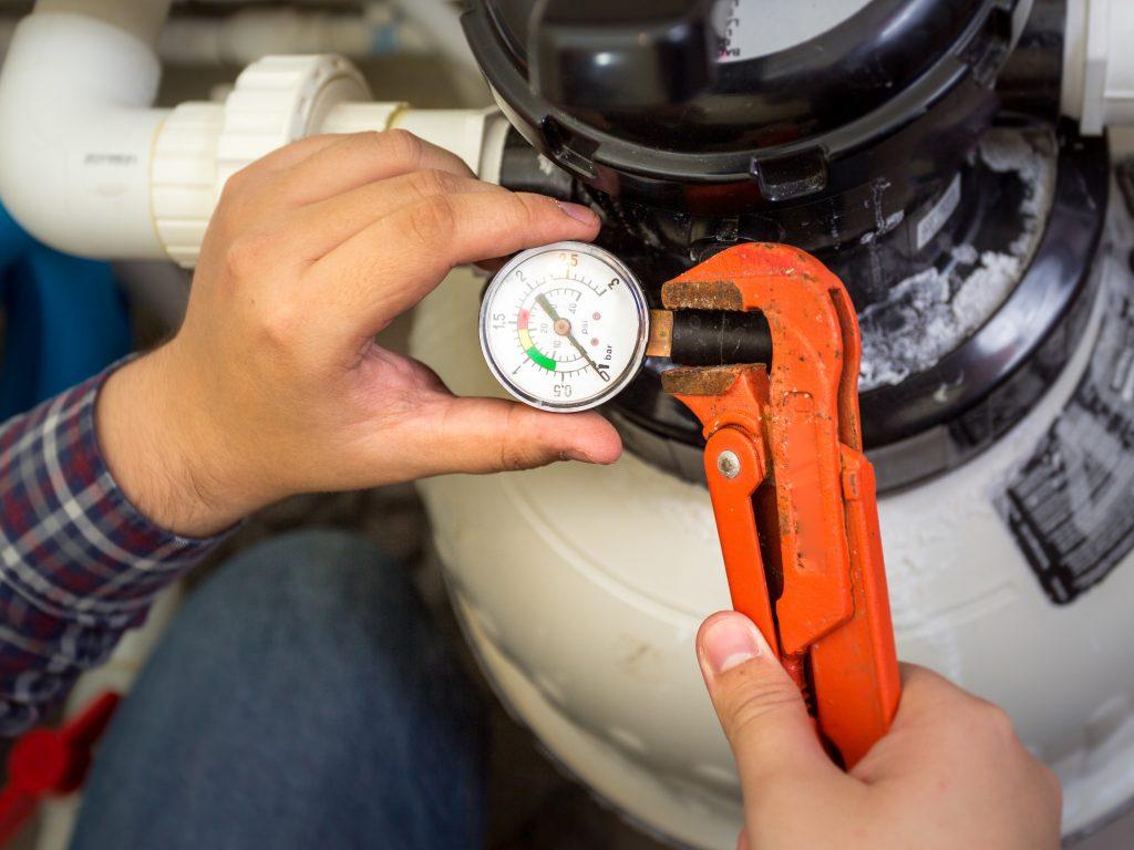 plumber installing manometer on pipe